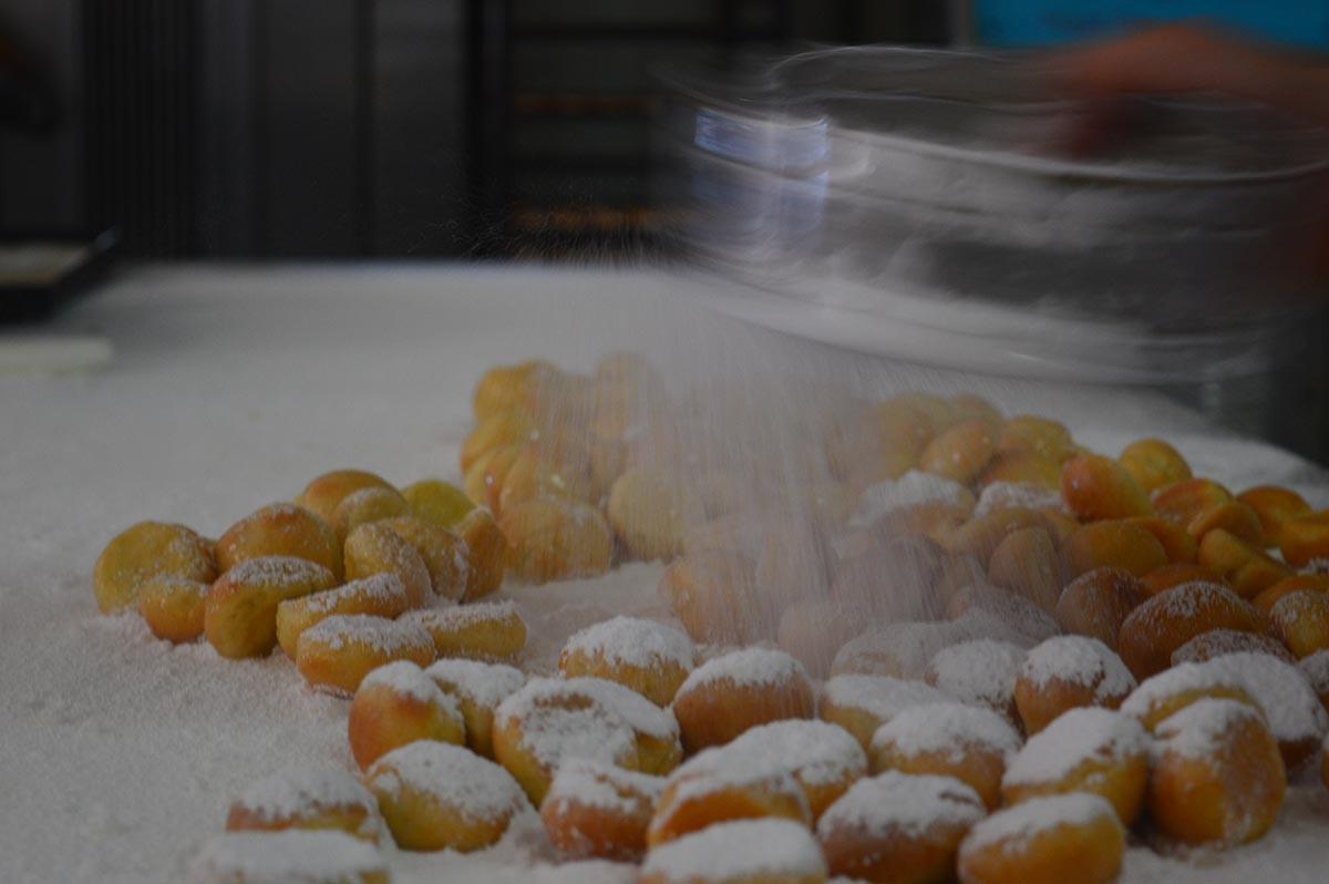 Preparazione dei dolci sardi: inzuccheramento dei pirichittos